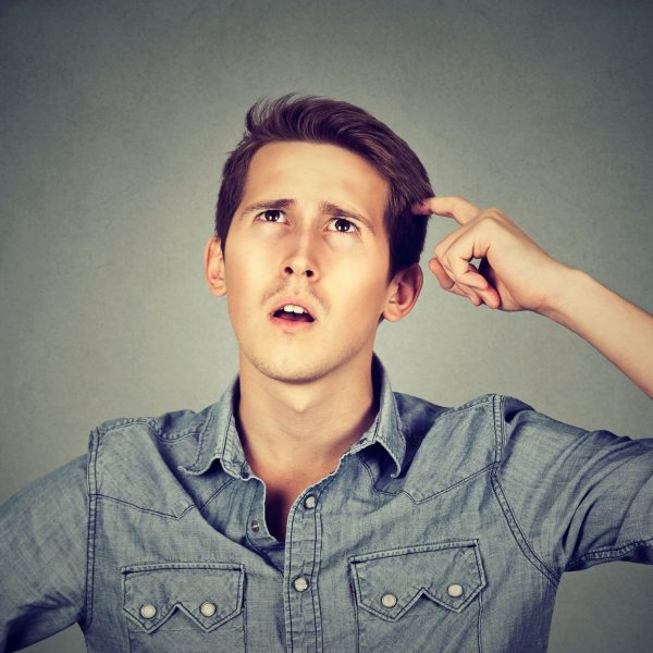 Man scratching head, thinking about something, looking up, isolated on grey wall background. Human facial expression, emotion, feeling